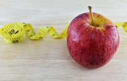 Red apple and yellow measuring tape concept for healthy diet and Royalty Free Stock Photos
