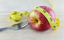 Red apple and yellow measuring tape concept for healthy diet and Stock Photos