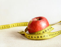 Red apple with yellow measuring tape. Dieting concept Royalty Free Stock Photos