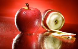 Red apples. Two wet red apples on a mirror and red background with droplets. One peeled stock photography