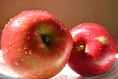 Red apples. 2 red Apple with drops of water on the plate Royalty Free Stock Photo