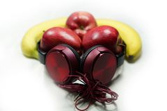 Red apples and banana with red headphones on white-background M royalty free stock image