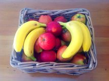 Red apples and bananas in the wicker basket Stock Image