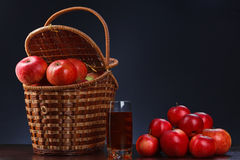 Red apples in a basket and apple juice. Horizontal Stock Images