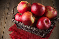 Red apples in basket. With napkin on rustic wood royalty free stock image