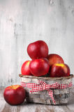 Red apples in basket. On rustic painted wooden background Royalty Free Stock Images