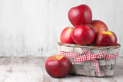 Red apples in basket. On rustic painted wooden background Royalty Free Stock Image