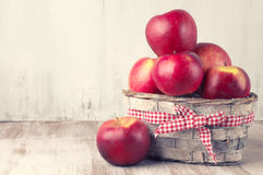Red apples in basket. On rustic painted wooden background. Toned image Royalty Free Stock Photography