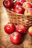 Red apples in a basket. On a rustic wooden board Royalty Free Stock Photo