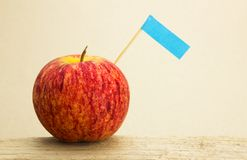 Red apples and blue label put on wooden with paper background Royalty Free Stock Photography