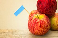 Red apples and blue label put on wooden with paper the backgroud Stock Image