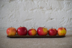 Red apples brick wall texture. Res yellow apples on wooden plate white brick wall background Stock Image
