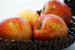 Red apples. Bunch of red apples on a black basket. all over a white table royalty free stock image