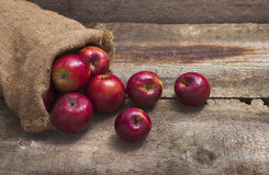 Red apples in burlap bag on wooden background Royalty Free Stock Photography