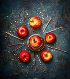 Red apples with chocolate coating and chopped almonds making on rustic wooden background Stock Photo
