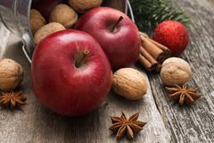 Red apples with christmas spices decoration on woden background. Red apples and walnuts with christmas spices decoration on woden background Stock Images