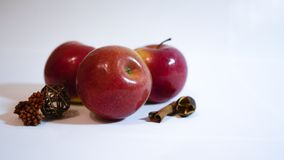 Red apples with cinnamon lie on a white table royalty free stock image