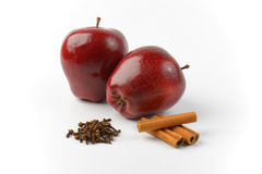 Red apples, cinnamon sticks and dried cloves Royalty Free Stock Photo