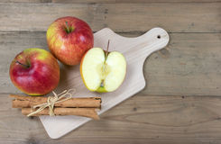Red apples and cinnamon sticks Royalty Free Stock Photos