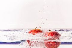 Red apples in clear water Royalty Free Stock Photos