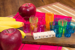 Red apples, colored glasses, bananas on wooden surface with the writing drinks Royalty Free Stock Photography
