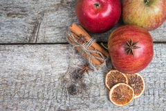 Red apples and dried spices on rustic wooden background. Christmas holidays Royalty Free Stock Image