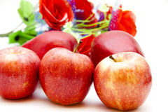 Red apples and floral decoration. On white background Royalty Free Stock Photography