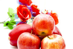 Red apples and floral decoration. On white background Royalty Free Stock Photo