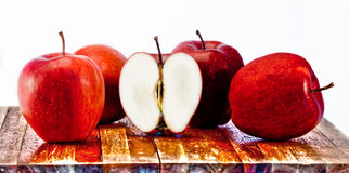 Red apples. Four red apples and half an apple on wooden cutting board Stock Photography