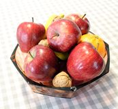 Red apples and fruit in the basket above the table Royalty Free Stock Photos