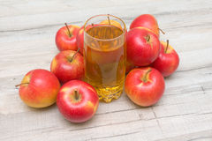 Red apples and glass of apple juice on a wooden table Royalty Free Stock Images