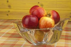 Red apples in a glass bowl on the kitchen table. Healthy food on the table. Autumn harvest of apples. Stock Photography