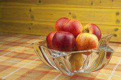 Red apples in a glass bowl on the kitchen table. Healthy food on the table. Autumn harvest of apples. Royalty Free Stock Photography