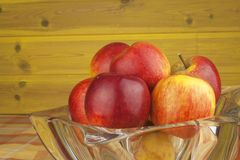 Red apples in a glass bowl on the kitchen table. Healthy food on the table. Autumn harvest of apples. Stock Photo