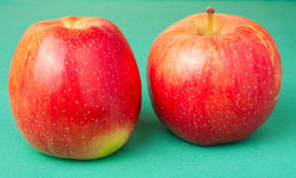 Red apples on green background Royalty Free Stock Image