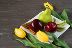 Red apples, green pear, sliced kiwi, sticks cinnamon and yellow tulips in white plate on grey wooden board. Royalty Free Stock Images