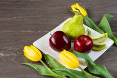 Red apples, green pear, sliced kiwi and yellow tulips in white plate on grey wooden board. Stock Image