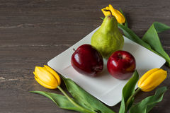 Red apples, green pear and yellow tulips in white plate on grey wooden board. Stock Photography