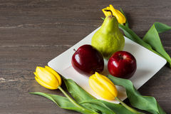 Red apples, green pear and yellow tulips in white plate on grey wooden board. Stock Images