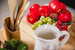 Red apples and green and red grapes in a plate on the surface of a wooden table royalty free stock images