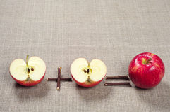 Red apples and halves. Red apple and two halves on background fabric stock image