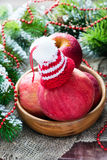Red apples with hat in bowl, festive decorations Stock Image