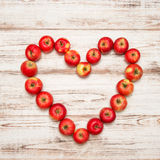 Red apples heart over wooden background. Love concept vibrant Stock Photo