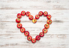 Red apples heart shape on wooden background. Valentines Day Stock Photos