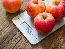 Red apples on kitchen scale on wooden background. Product weighing.  royalty free stock image