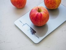 Red apples on kitchen scales on white background. Product weighing.  royalty free stock photo