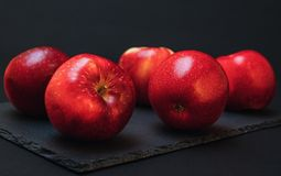Red Apples on a kitchen table with black background royalty free stock image