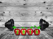 Red apples and large dumbbell on wooden planks. Healthy resolutions for the New Year 2018 Stock Images