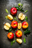 Red apples with leaves on stone background. Royalty Free Stock Photo