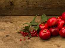 Red apples with leaves on wooden background Royalty Free Stock Photos